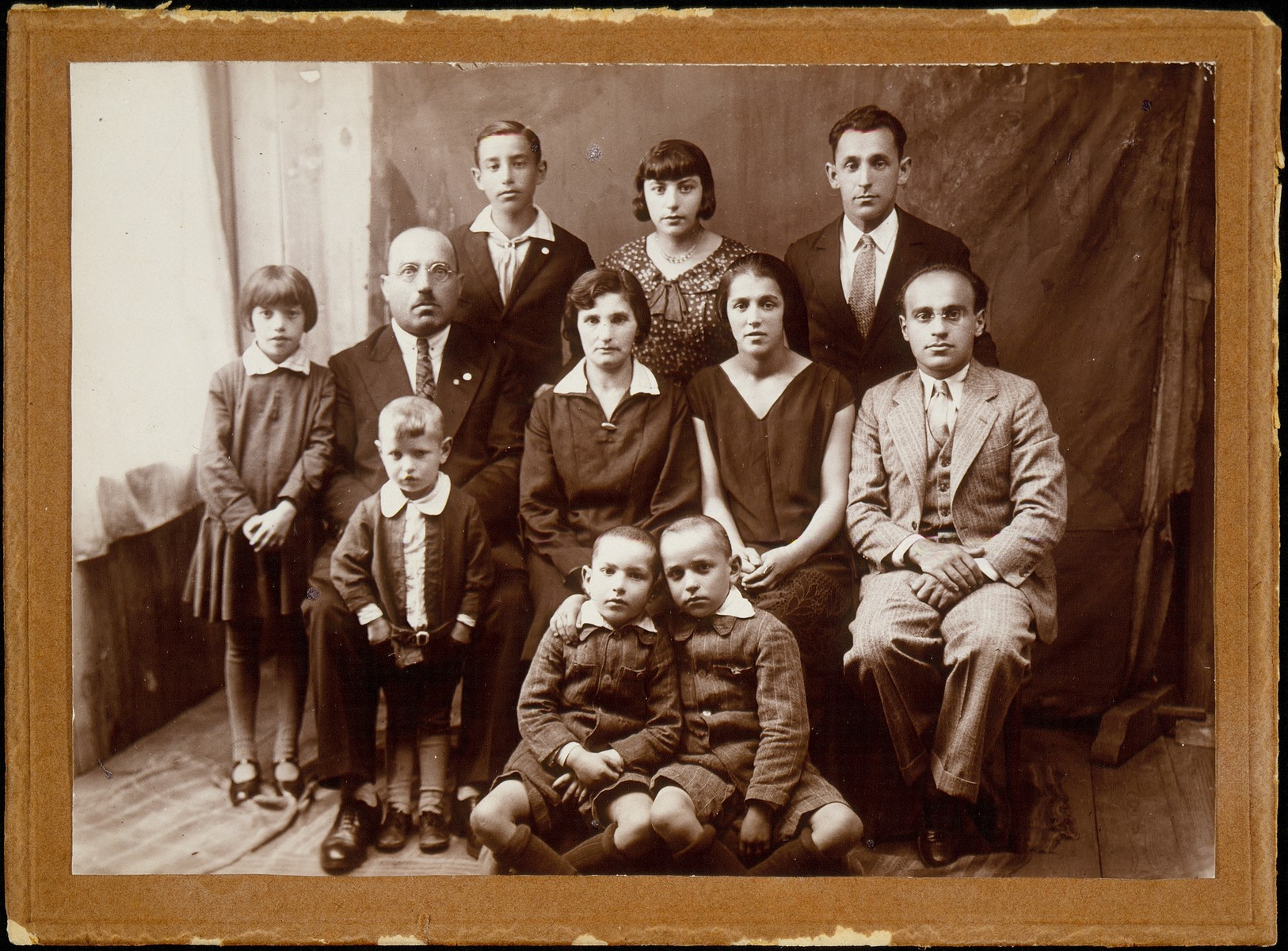 The family of the school principal Moshe Yaakov Botwinik.  (top row, right to left) Layzer, a relative; daughter Fania; and son Leibke;  (middle row, right to left) two  relatives named Rakow; Shoshana and Moshe Yaakov.  Standing in front of his father is the youngest son, Avremele; next to him is a daughter Zipporah.  Sitting on the floor are sons Hillel (right) and Yitzhak.