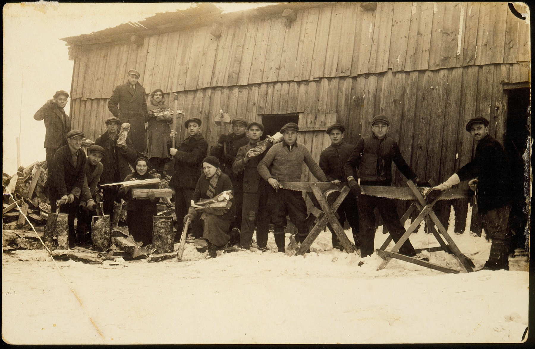 Members of the Hehalutz hachshara in Oszmiana saw wood in the lumberyard.