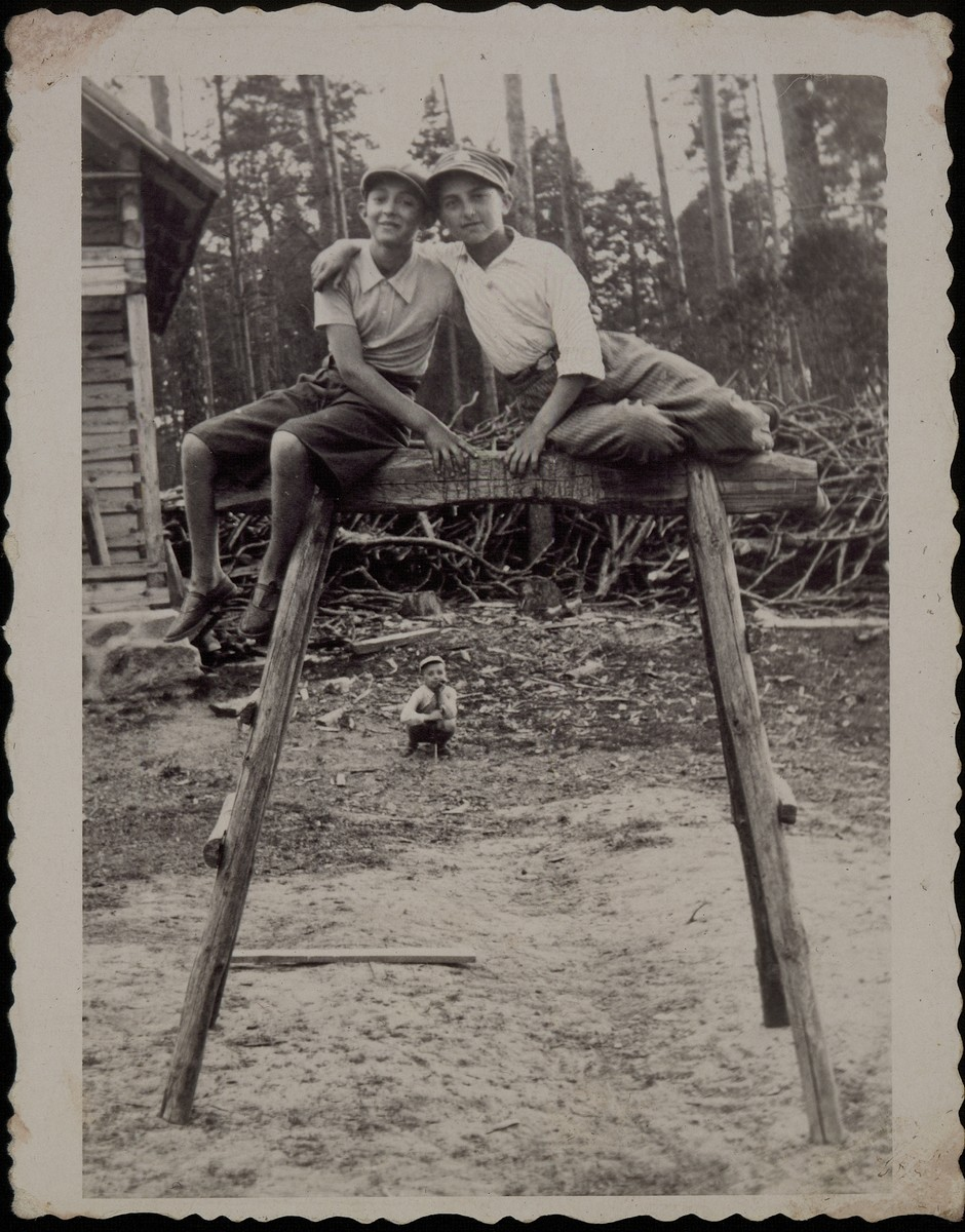 Bezalel Charney (left) sits with a friend on a wooded frame in a Jewish farm in Eisiskes.  Both boys were murdered by the Germans in the September 1941 mass killing action in Eisiskes.