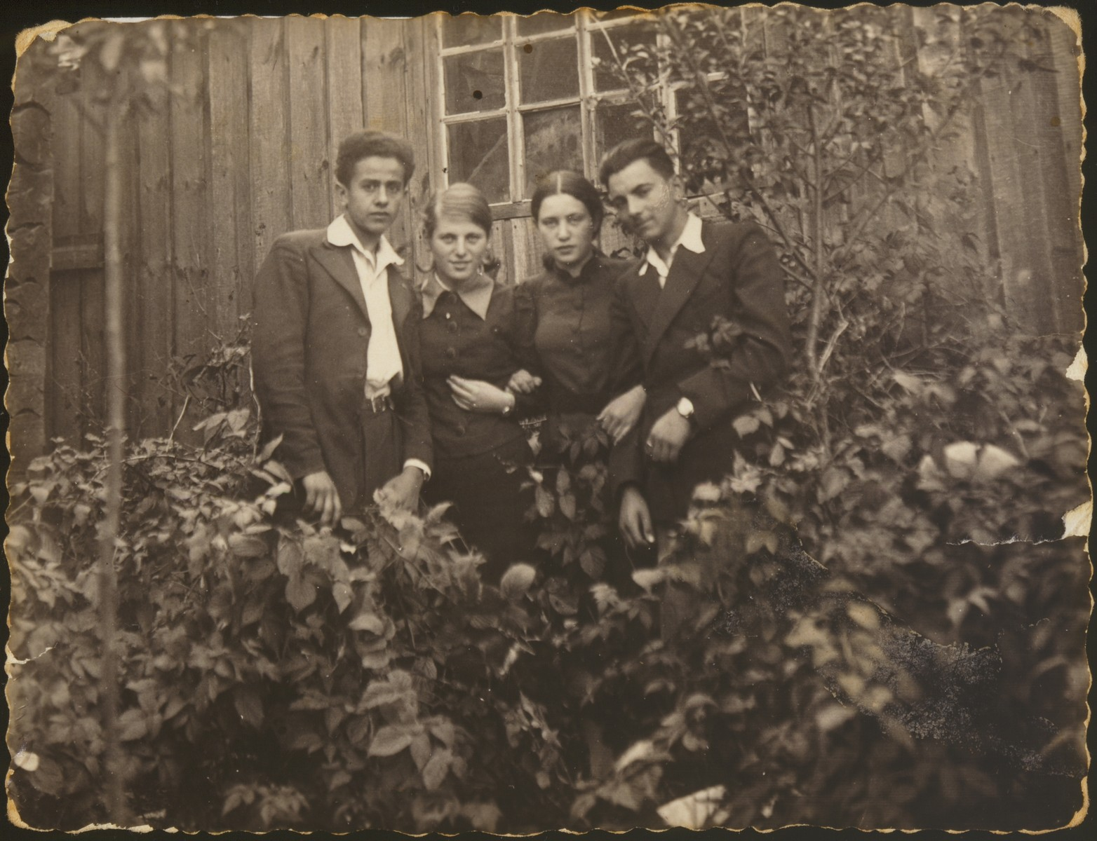 """Breine Plotnik stands with three friends in front of her house.   Breine Plotnik is standing second from left.  The photo was inscribed in Yiddish,  """"In memory for Hayya Sarah Plotnik from me your sister friend and friend Breine Plotnik, Eishyshok.  January 1, 1938."""""""
