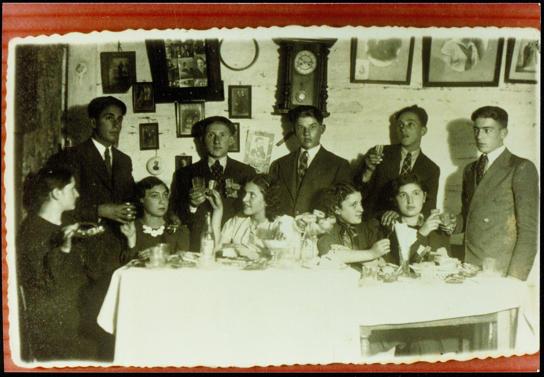 Young people gather around a dining room table at a party.