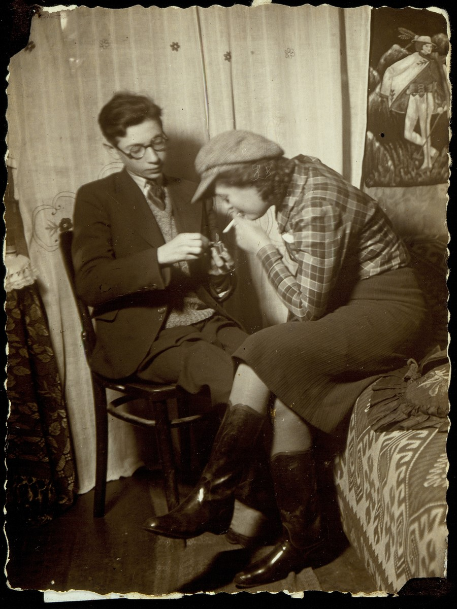 A Jewish teenager lights a cigarette for his girlfriend in her room in Eisiskes.  The young woman is Elka Lubetski.  The name of the young man is unknown, but he was a student at the Hafetz Hayim yeshiva.  Both were members of the illegal communist party.  The couple eventually married, but their fate is unknown.