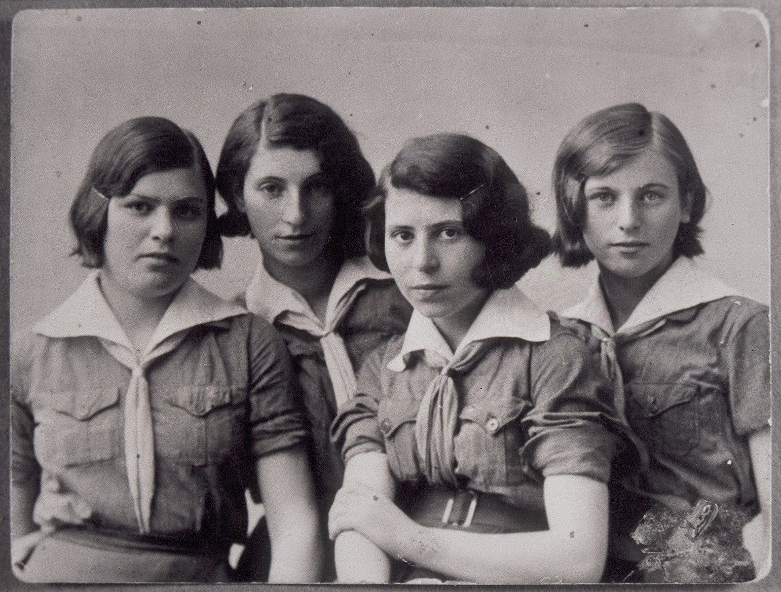 Four Jewish teenage girls who are members of the Hashomer Hatzair Zionist youth movement in Eisiskes, pose in their uniforms.  Pictured from right to left are: Breine Plotnik, Sara Ginunski, name unknown and Mikhele Plotnik.  All were killed by Germans during the September 1941 mass shooting action in Eisiskes.