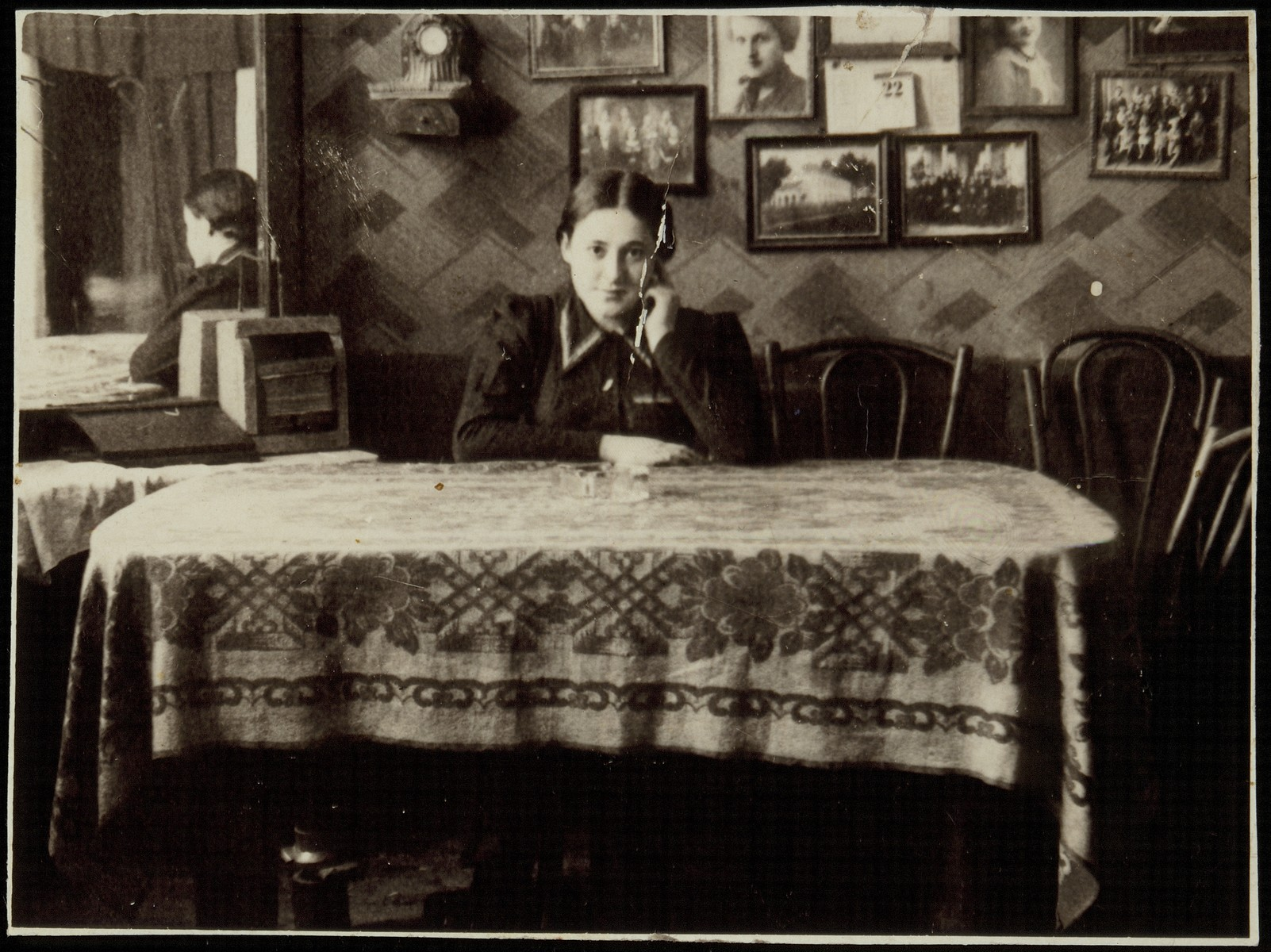 Rivka Pruskin Cofnas sits at a dining room table in the house of the photographer, Rephael Lejbowicz.