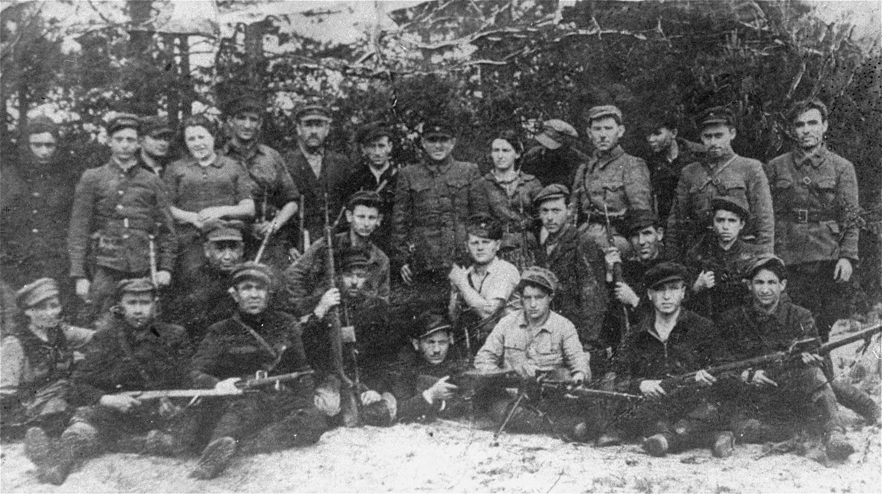 A group of partisans from various fighting units including the Bielski group and escapees from the Mir Ghetto on guard duty at an airstrip in the Naliboki Forest.  Among those pictured is Commander Nowiczki, standing first on the right; Joseph Kozlowski (now Kazlow), top row, second from right;  Solomon Golanski is pictured at the bottom right; Josef Kessler is in the center wearing a short white sleeve shirt;  [Behind him might be Hershl Goldhamer; Seated in the center might be Esia Schorr (a cousin of the Bielskis)]; Standing second from the left is  Zeev Schriber; Sitting third from the left (below the standing woman partisan ) is Berkowitz; both from Mir Ghetto;  Gershon Seigel (b. 1926, Slonim) is standing third from the right.  Yehuda Bielski (later Bell) is lying down with his gun in the front row, center.  Pictured seated second from the right is Saul Schadnow.
