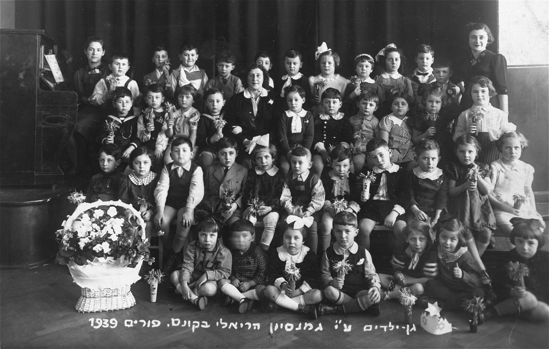 "Group portrait of a kindergarten class at the Reali Hebrew gymnasium in Kovno dressed in costume for a Purim performance.  The Hebrew caption reads, ""Kindergarten of the Reali Hebrew gymnasium in Kovno, Purim 1939.""  Among those pictured is Motel Ginzburg (second row from the front, sixth from the right), a cousin of the donor who perished during the war."