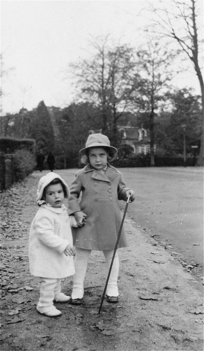 Two young Jewish children stand on the sidewalk dressed in hats and coats.  Pictured are Yoka and Francisca Verdoner.