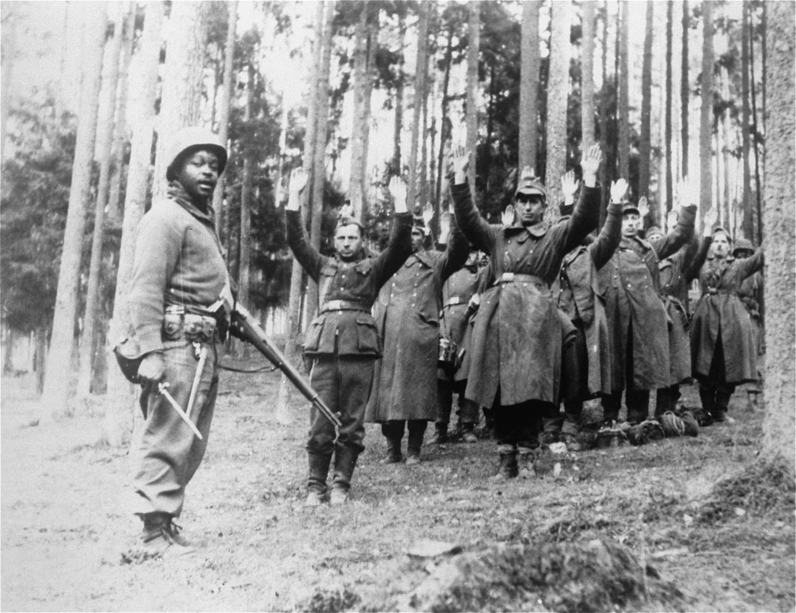 An African-American soldier with the 12th Armored Division, Seventh U.S. Army, stands guard over a group of German soldiers captured in the forest.
