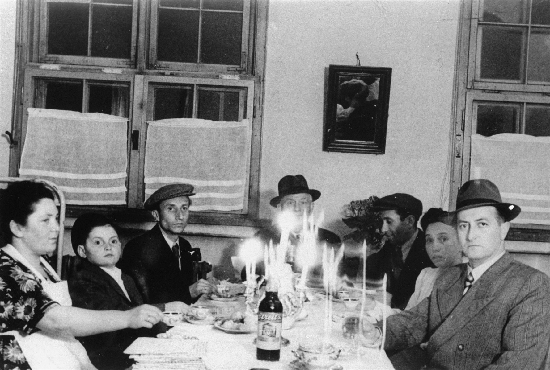 The Gurfein family attends a Passover seder at the Landsberg displaced persons camp.    Pictured from left to right are:  Basia (Gurfein) Berliner; Itzhak Gersten (her nephew); Nathan Berliner; and four other Polish Jews.