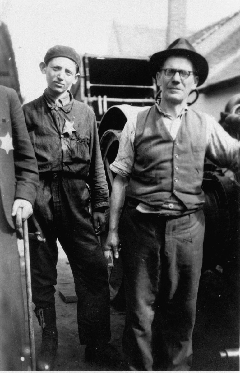 A father and son, wearing a Jewish badge, in front of their machine shop in the Debrecen ghetto.  Pictured are Moritz and his son Endre Goldstein.  Moritz and Matilde Goldstein had four sons, Alex (b. 1914), Ernst (b. 1918), Miklos (b. 1920), and Endre (b. 1928).  Moritz died while serving in a Hungarian labor brigade. In April 1944, Matilde, Ernst and Endre were deported to Auschwitz, where the mother and her youngest son were gassed immediately.  Ernst was imprisoned for a time in Auschwitz before being sent to a series of concentration camps in Germany.  He survived the camps and eventually emigrated to the U.S. in 1946.