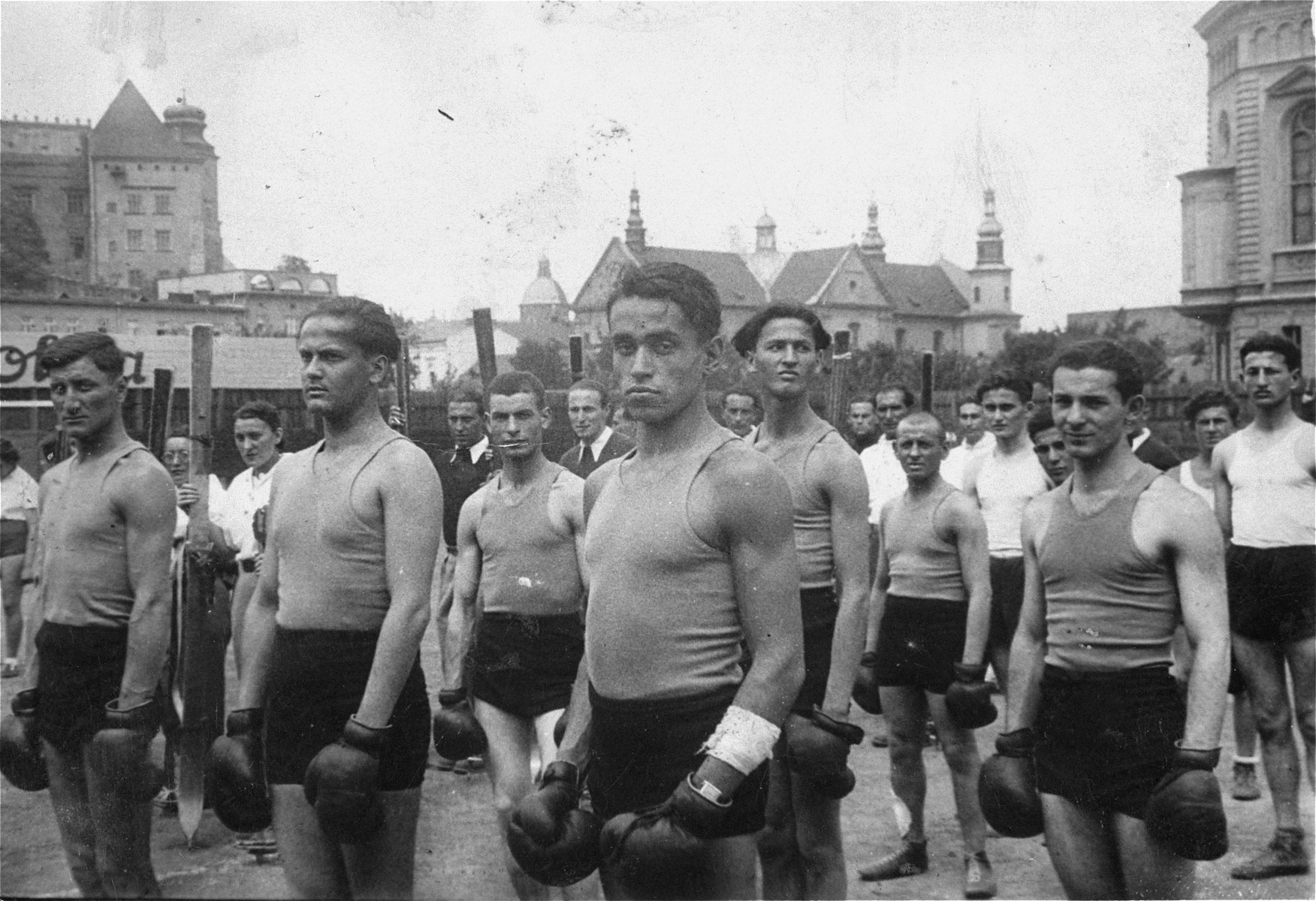The Maccabi boxing team stands in formation wearing their boxing gloves in a square in Krakow.  Among those pictured is Fred Eichner (second row, far right).