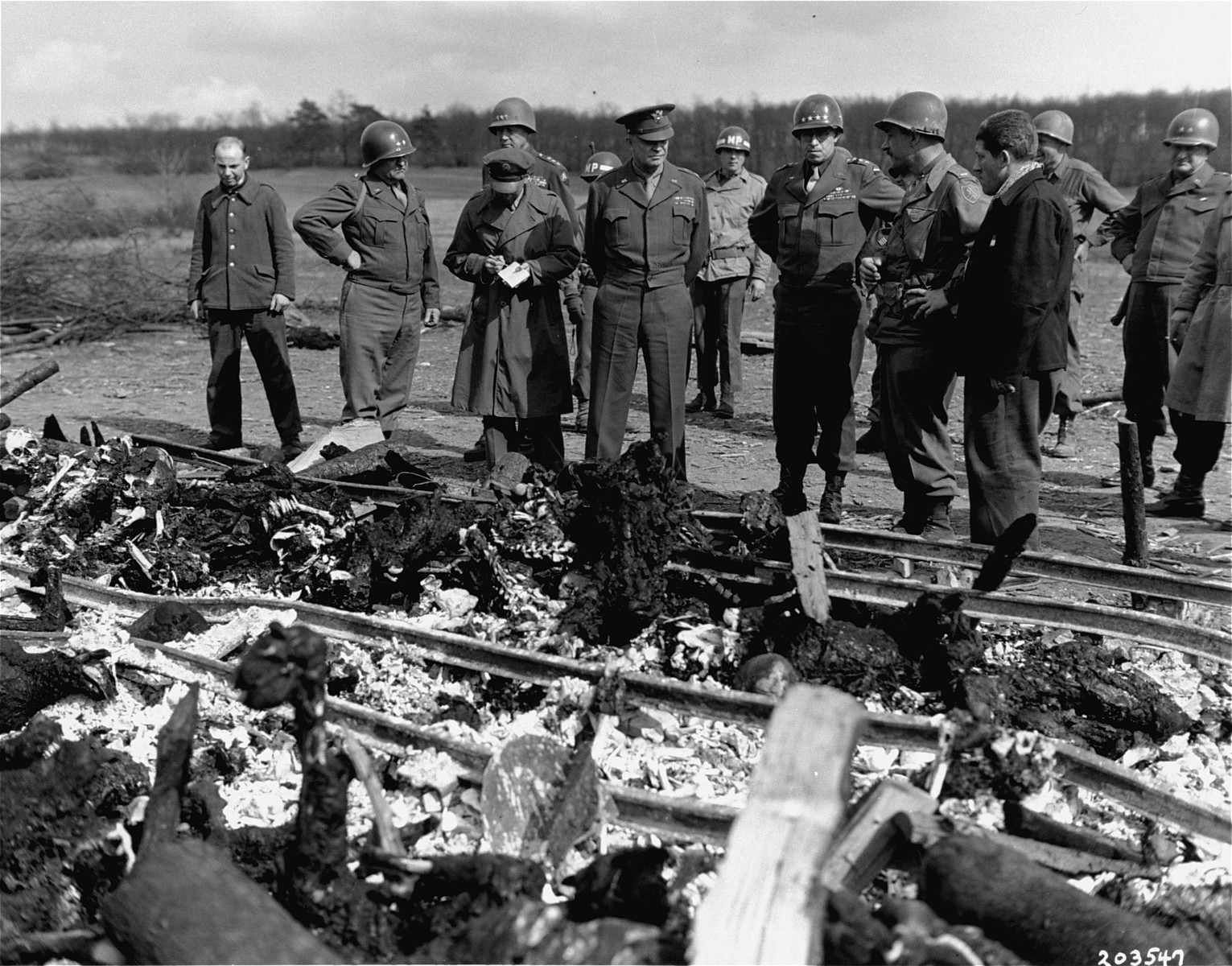 "While on an inspection tour of the newly liberated Ohrdruf concentration camp, General Dwight Eisenhower and a party of high ranking U.S. Army officers, including Generals Omar Bradley, George Patton, and  Manton Eddy, view the charred remains of prisoners that were burned upon a section of railroad track during the evacuation of the camp.  Also pictured is Jules Grad (third from the left taking notes), correspondent for the ""Stars and Stripes"" U.S. Army newspaper and 1LT Alois Liethen, acting as interpreter; ."
