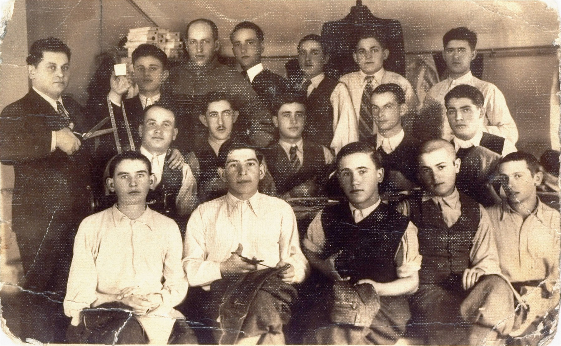 Abraham and Ludvic Ickovic pose with the employees of their garment factory, the Pansky a Damsky Krejci, in Tacovo.  Abraham Ickovic is pictured at the left holding a pair of scissors; Ludvic stands next to him.