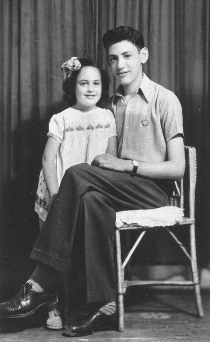 Studio portrait of two Jewish siblings who have been expelled from Sofia, Bulgaria to the provinces.  The boy is wearing a Jewish badge.  Pictured are Norbert and Odette Yasharoff.