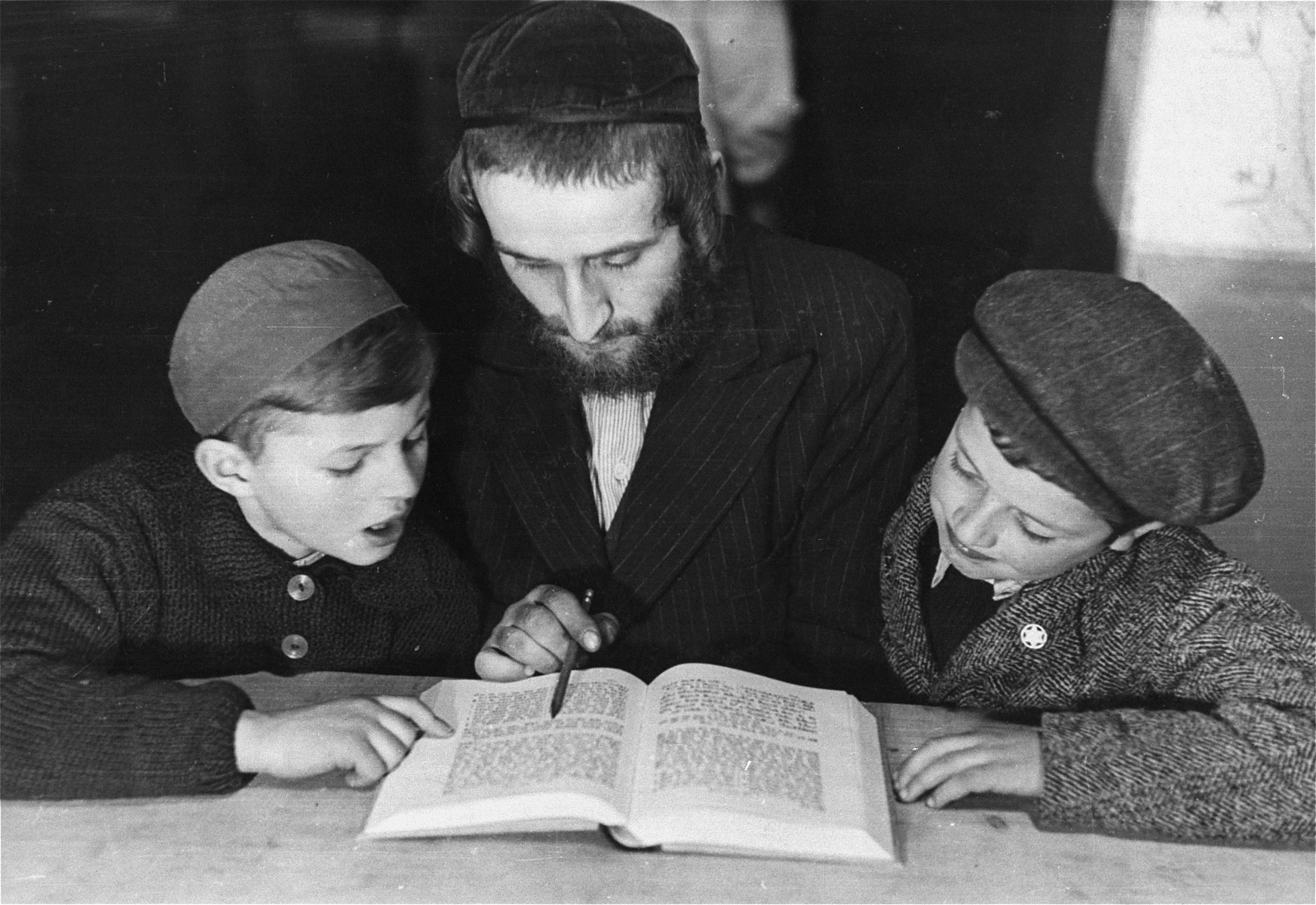A teacher reviews a religious text with two boys in the Landsberg displaced persons' camp.