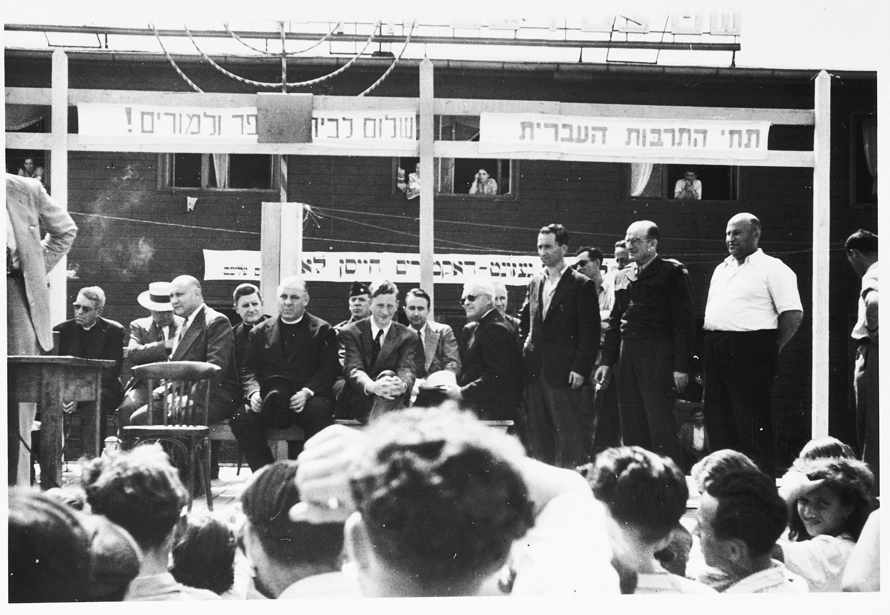 "Jewish DP leaders and invited guests are assembled on a podium at an outdoor public meeting [probably in the Schlachtensee displaced persons camp].  The Hebrew banners at the top read, ""Long live the Hebrew culture,"" and ""Welcome schools and teachers!"""