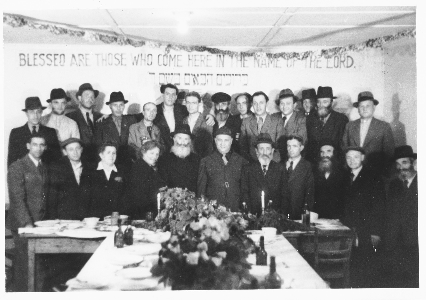 UNRRA camp director Harold Fishbein poses with a group of religious Jews at a holiday celebration in the Schlachtensee displaced persons camp.  Harold Fishbein is standing in the front row center, between the two bearded men.  Also pictured is Benjamin Holzer in the first row, on the far left.