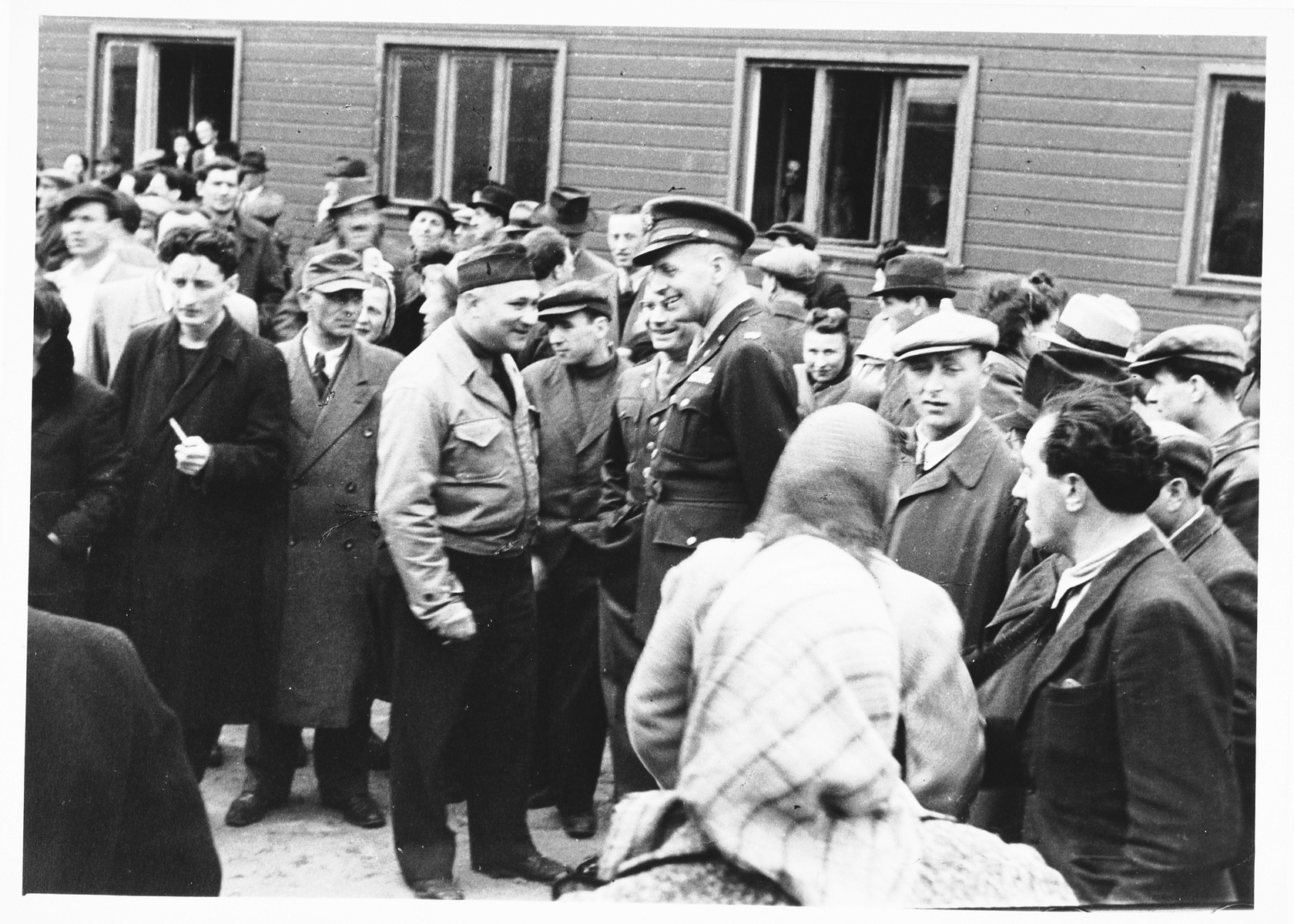 UNRRA camp director, Harold Fishbein (in the light jacket), converses with an American military officer amid a crowd of Jewish DPs outside a barracks in the Schlachtensee displaced persons camp.    Moise Finkelsztajn is on the right.