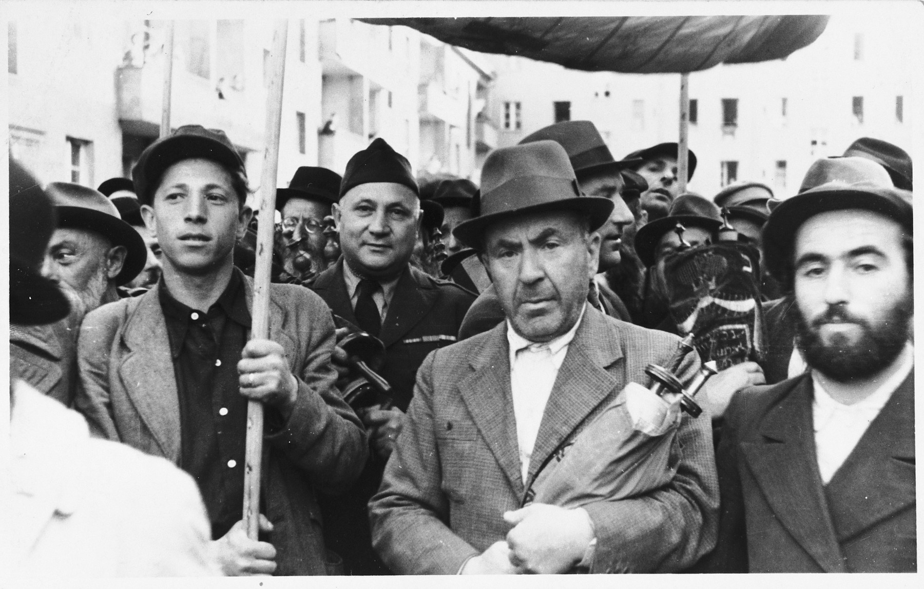 Jewish DPs carry small torah scrolls beneath a canopy in a procession along the main street of the Marienburg displaced persons camp.  Among those pictured is Harold Fishbein (center, left, wearing a tie).