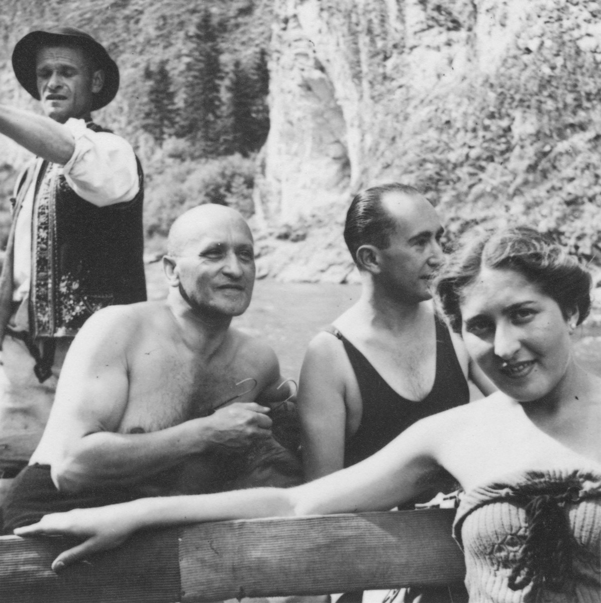 Samuel File, a Jewish businessman from Bielsko-Biala, Poland, relaxes outside on the banks of a river with his wife and friends during a summer vacation.  Pictured are Samuel File (seated at the left) and Edyta File (front, right).