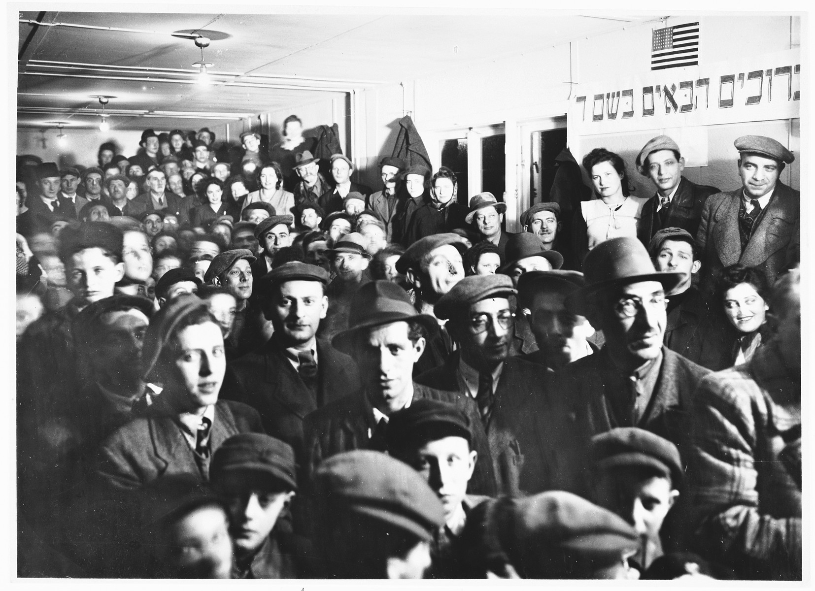 """A crowd of Jewish DP men, women, and children attend a meeting in a hall in the Schlachtensee displaced persons camp.   The Hebrew banner on the wall, which features an American flag, reads, """"Welcome in the name of God."""""""
