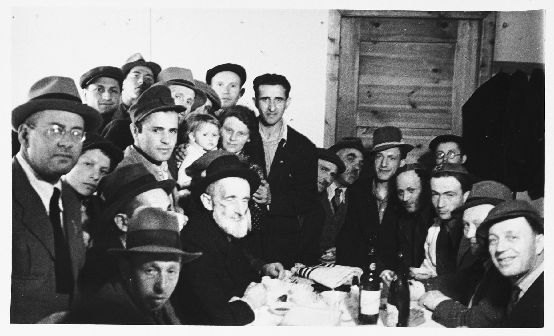 A group of religious Jewish DPs crowd around a table set with food and bottles of wine at the Schlachtensee displaced persons camp.