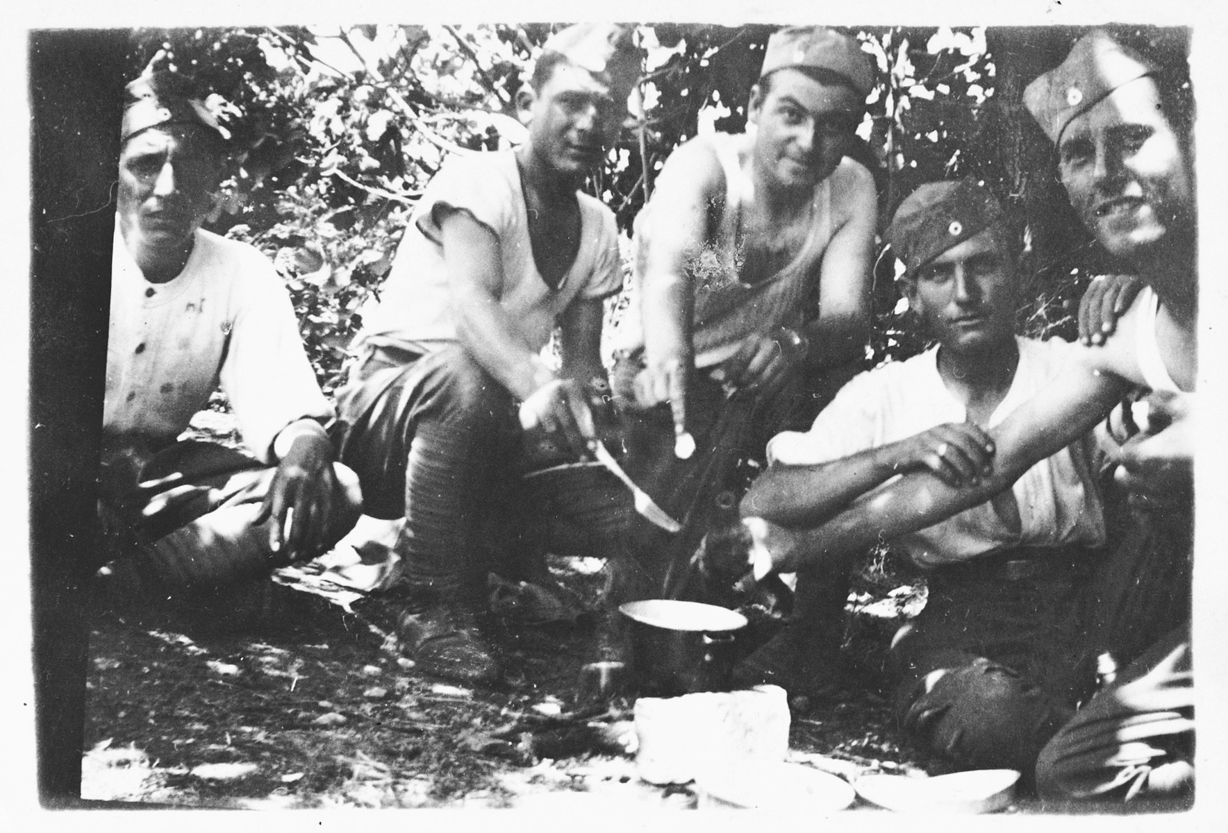 A group of Greek POWs, including some Jews, cook dinner outdoors during their captivity.
