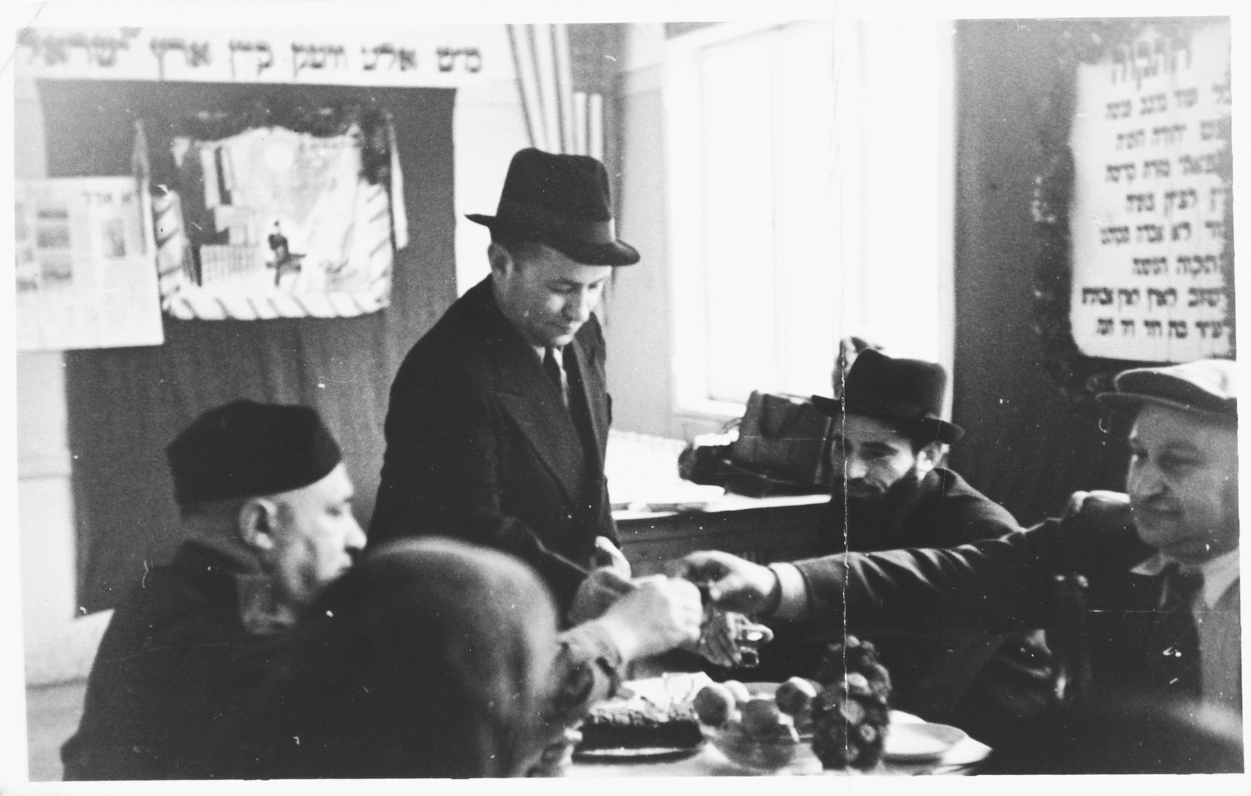 "UNRRA camp director Harold Fishbein shares a toast with a group of religious Jews at a circumcision ceremony in the Schlachtensee displaced persons camp.  Harold Fishbein is seated on the left.  The Yiddish caption on the back of the photo reads, ""Our beloved director at the bris [circumcision] of our [illegible] Barschap, 29/III/47."""