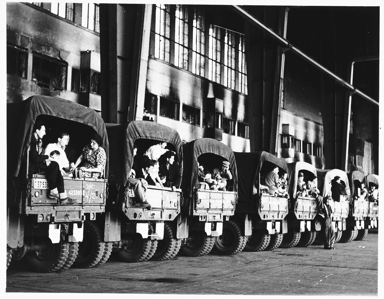 Canvas covered trucks packed with Jewish DPs [who are being evacuated to Frankfurt am Main during the Berlin Blockade] are parked in a row [probably at a Berlin airport].