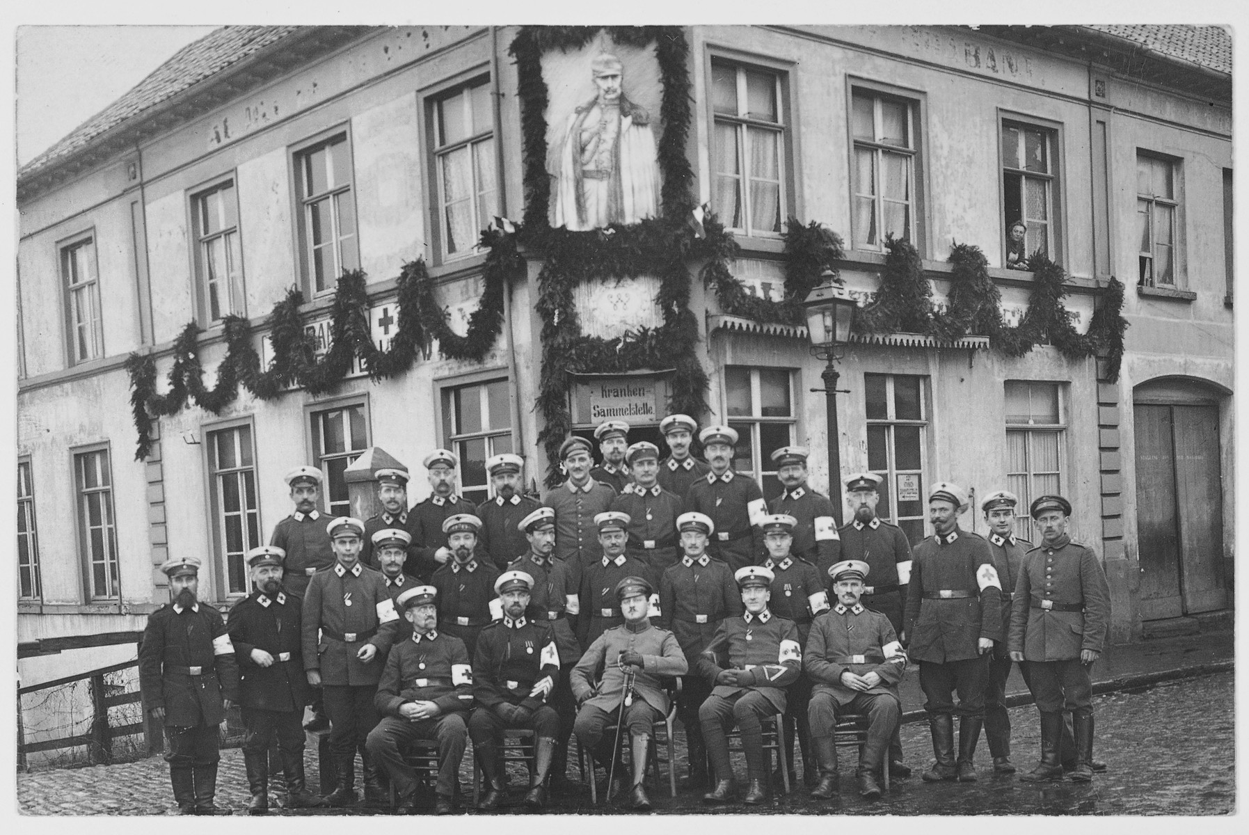 Group portrait of doctors who have been mobilized for the war effort, beneath a portrait of the Kaiser outside a hospital.
