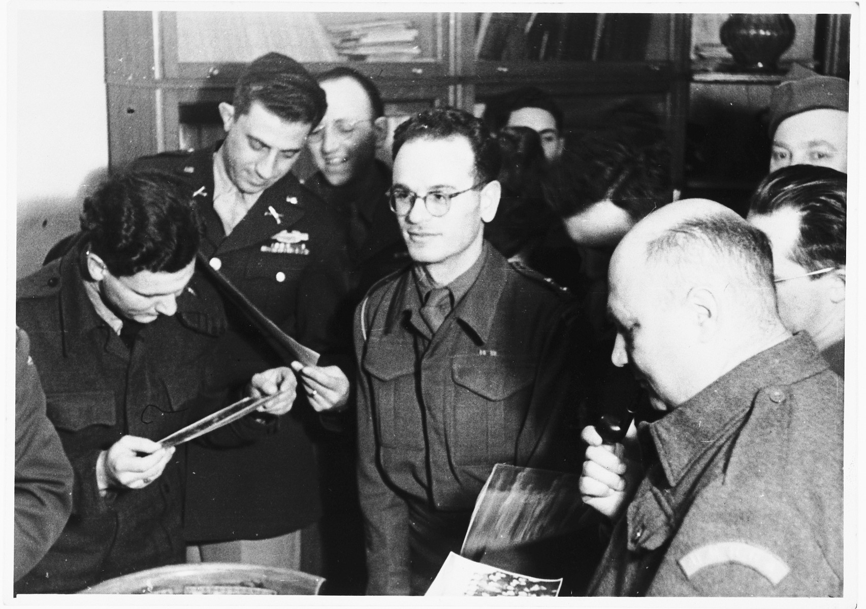 UNRRA camp director Harold Fishbein (lower right) and other personnel view photographs in an office in the Schlachtensee displaced persons camp.