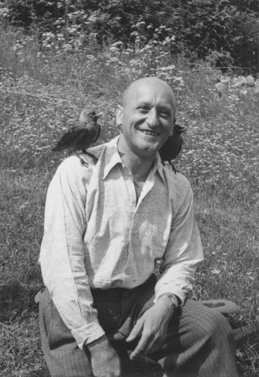 Samuel File, a Jewish businessman from Bielsko-Biala, Poland, poses outside with a bird on each shoulder during a summer vacation.