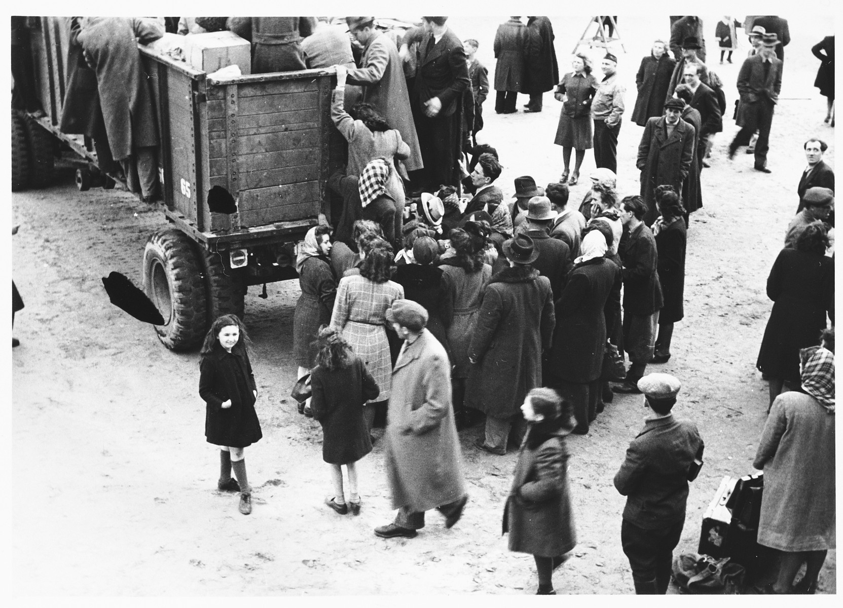 Jewish DPs board open trucks during their departure from the Schlachtensee displaced persons camp.