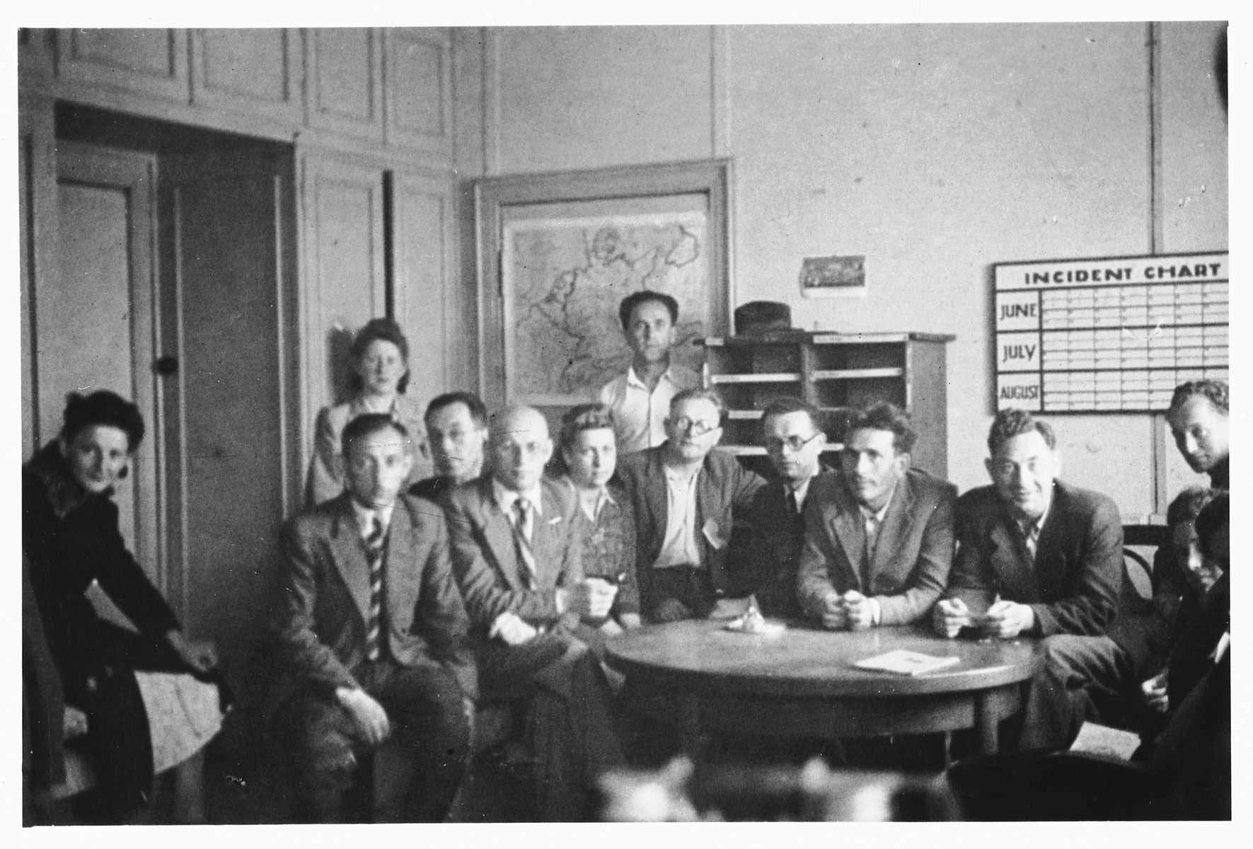 [Group portrait of members of the administrative staff in an office in the Schlachtensee displaced persons camp.]