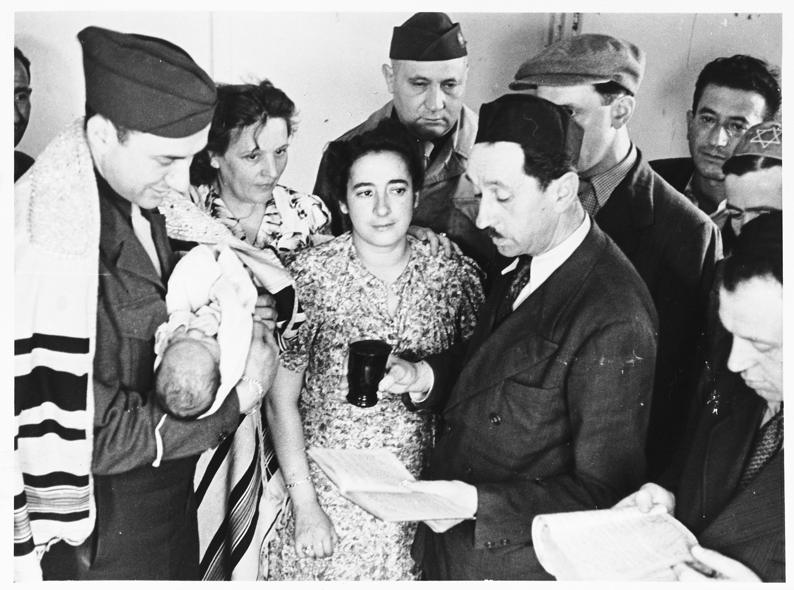 A blessing is recited during a circumcision ceremony in the Schlachtensee displaced persons camp.  Among those pictured is UNRRA camp director Harold Fishbein (center, back).