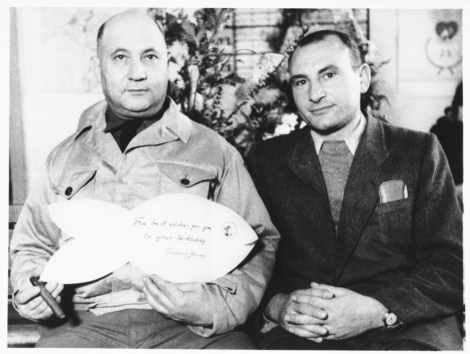 UNRRA camp director, Harold Fishbein (left), holds up a birthday card shaped like a fish, which he received from the children in the Schlachtensee displaced persons camp.  Pincus Proszowski (later Peter Prosaw) is pictured on the right. A survivor of the Lodz ghetto and Auschwitz, he was the director of the Schlachtensee children's home and the graphic designer who made the camp scrapbook.