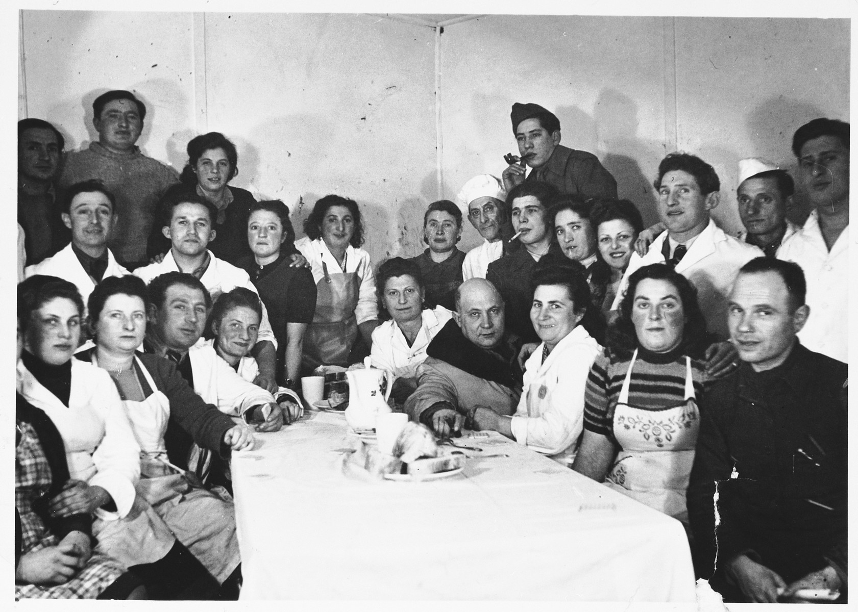 Group portrait of Jewish DPs gathered around a table in the Schlachtensee displaced persons camp.