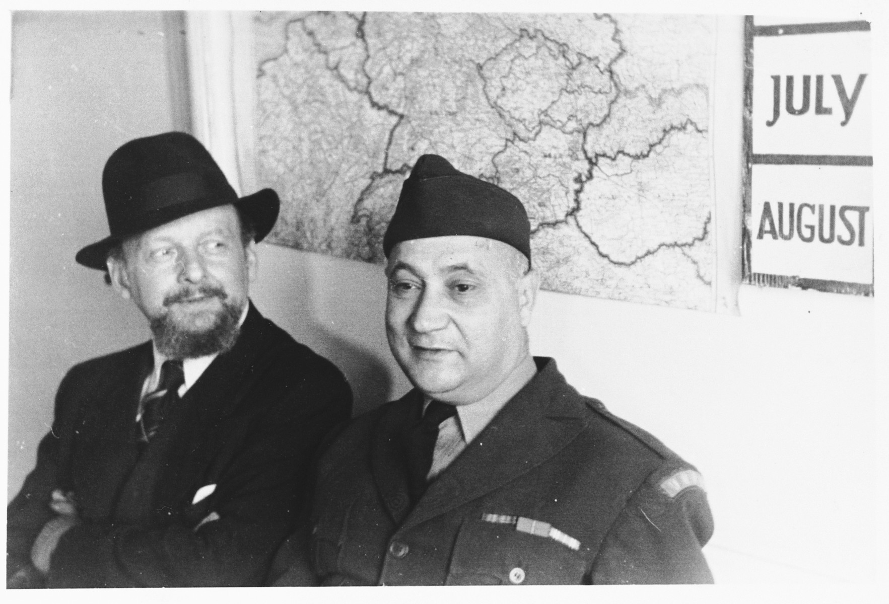 UNRRA camp director Harold Fishbein poses with a civilian in front of a map of Europe in the Schlachtensee displaced persons camp.