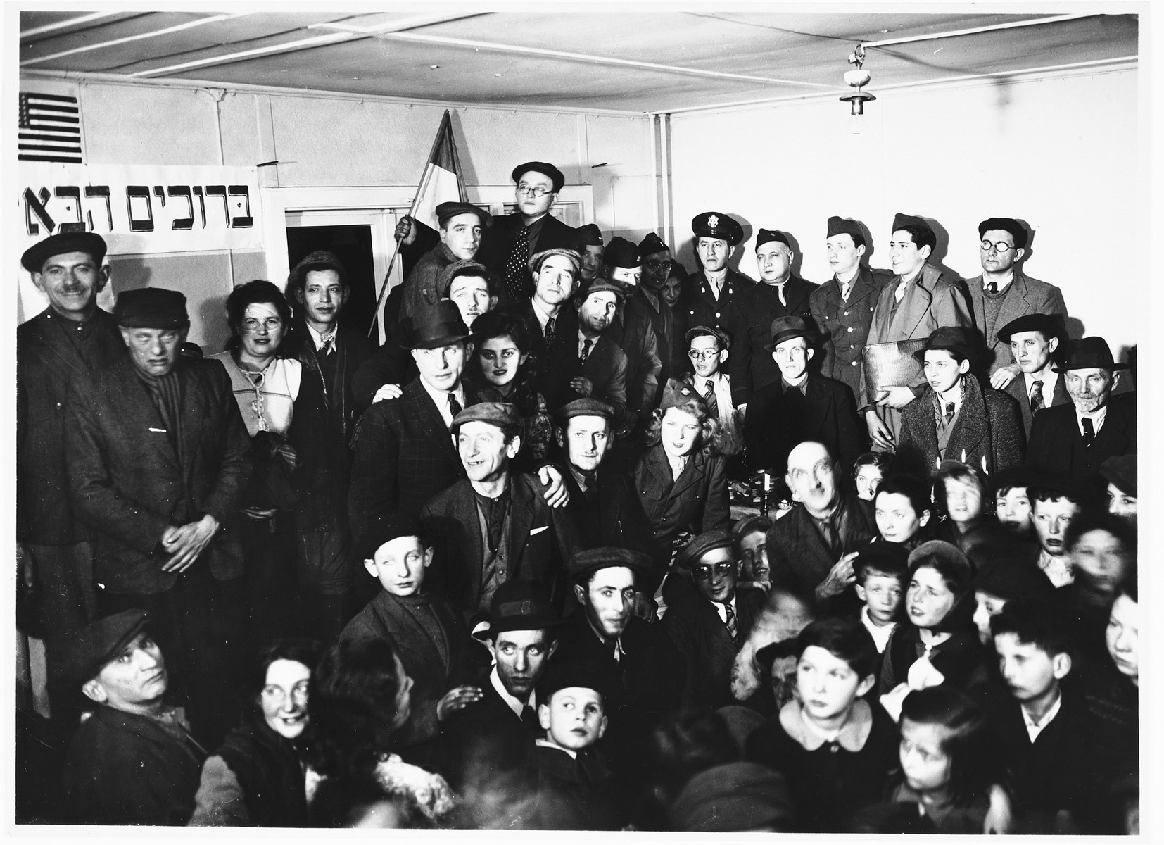 "A crowd of Jewish DP men, women, and children attend a meeting in a hall in the Schlachtensee displaced persons camp.  The Hebrew banner on the wall, which features an American flag, reads, ""Welcome in the name of God."""