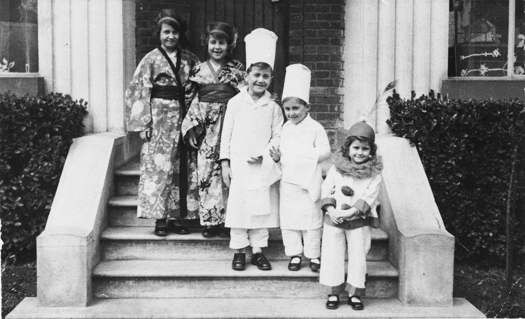 The Feist children pose on the steps of their home dressed in Purim costumes.  Pictured from left to right are: Selma, Judith, Martin, Jacob and Ellen Feist.