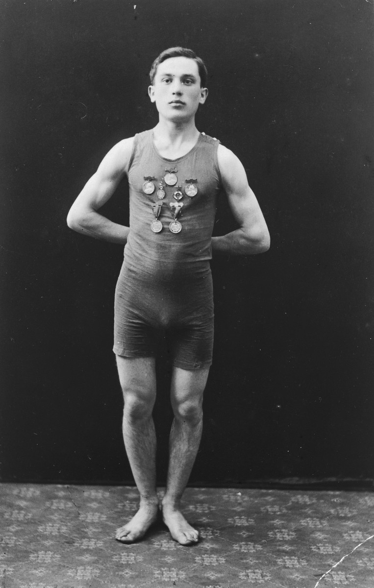 Portrait of swimmer Josef Ginsburg sporting several medals after swimming across the English Channel for Denmark.  Originally from Poland, Josef lived in Denmark before immigrating to Germany.