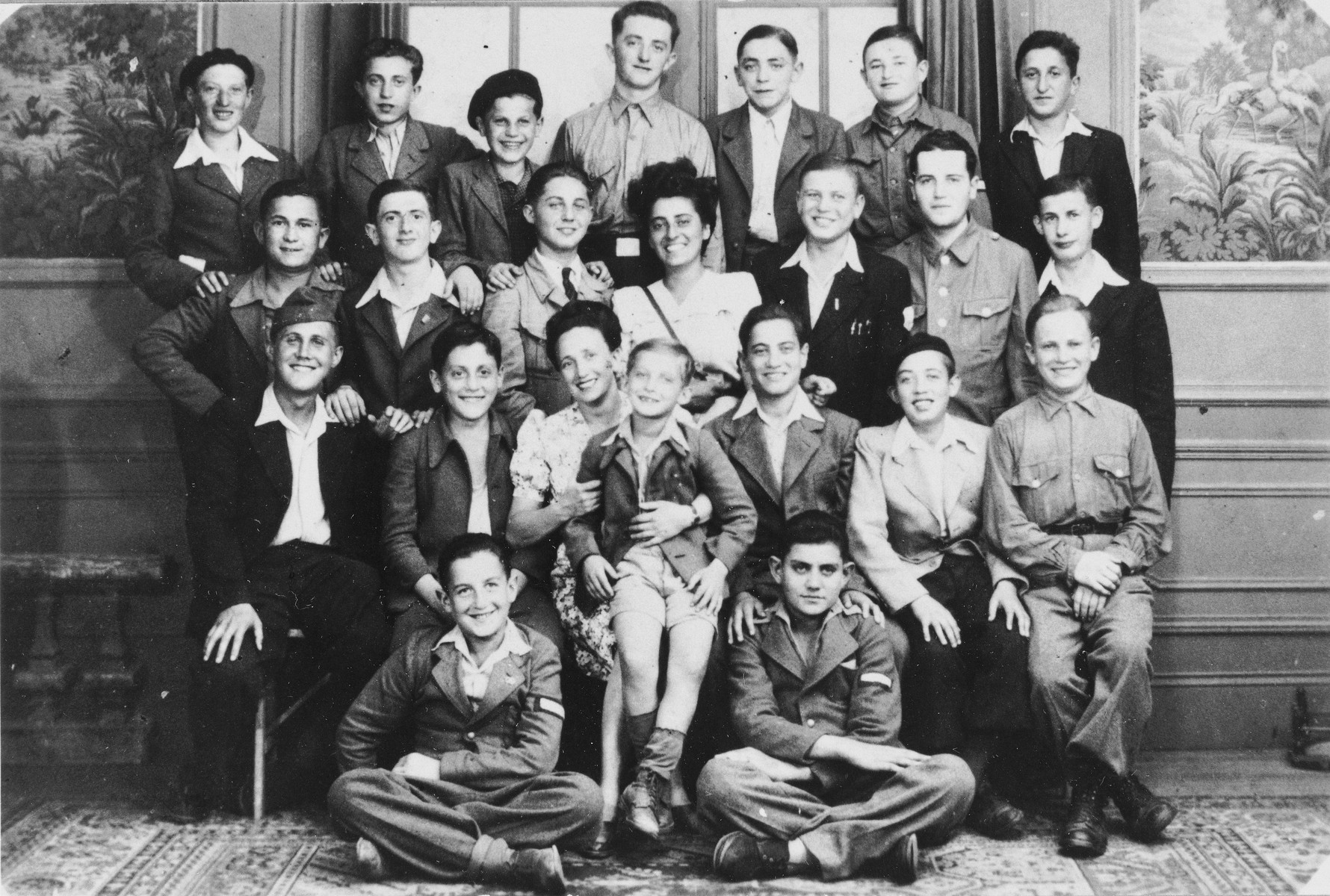 Group portrait of OSE staff and Jewish DP youth who numbered among the Buchenwald children, at an OSE (Oeuvre de Secours aux Enfants) children's home in France [either in Ambloy or Taverny].  Among those pictured is Mme Gaby Wolff-Cohen (second row from the top, in the center).  Top row, second from left is Abraham Tuszynsky from Piotrokow Trybunalski., and Solomon Hans third from right. Seated on the lap of the other woman is Izio Rosenman from Demblin.  Jakob Rybsztajn is seated in the same row second from the right.  First Seated Row , third from the rght is Saul Fruchter