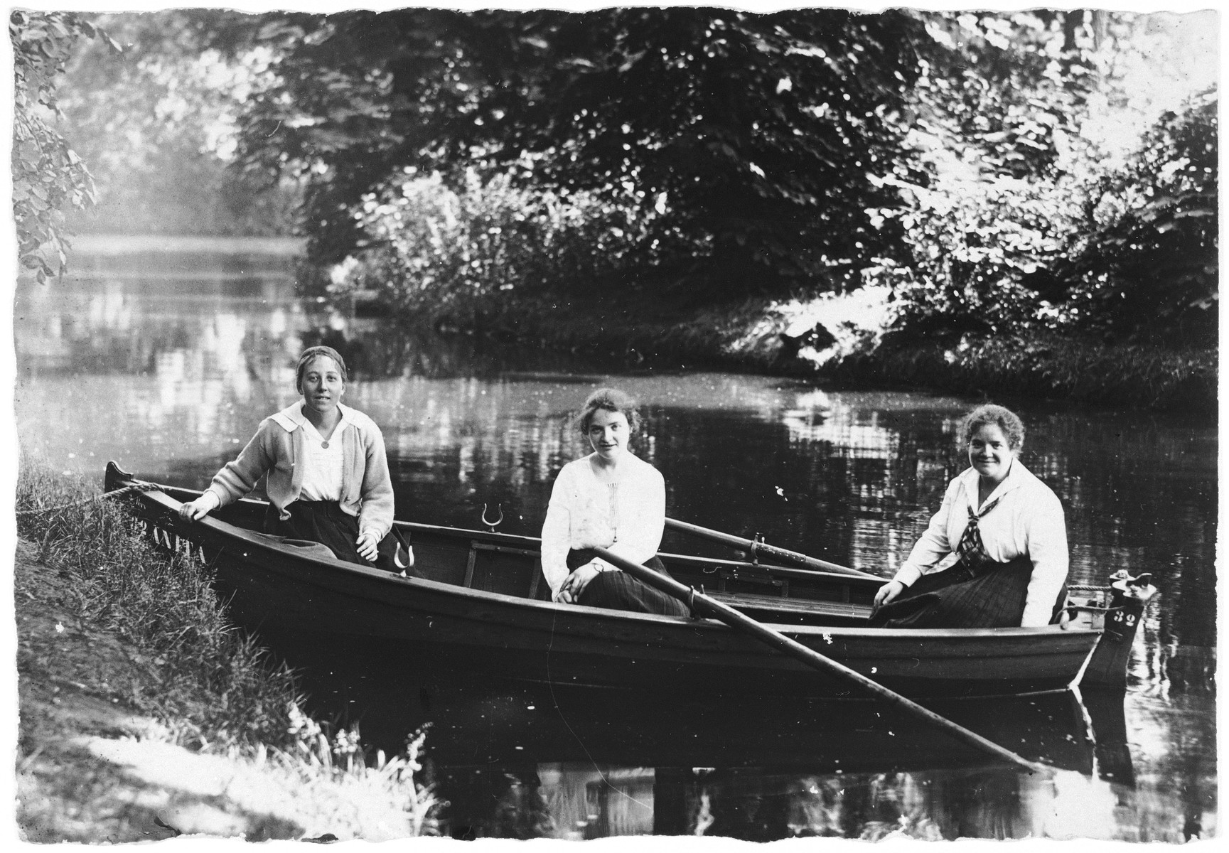 Three young Jewish women sit in a rowboat on a lake or river in Bad Homberg, Germany.  Hannah Feist is pictured on the left [probably with her sisters].