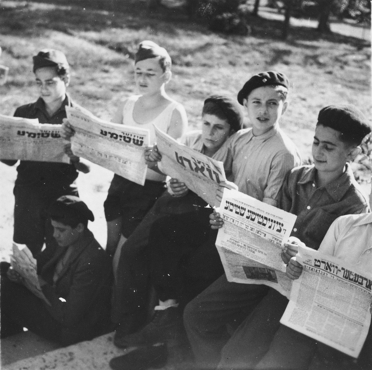 Jewish DP youth who numbered among the Buchenwald children, read an assortment of Yiddish newspapers outside on the grounds of an OSE (Oeuvre de Secours aux Enfants) children's home in France [either in Ambloy or Taverny].