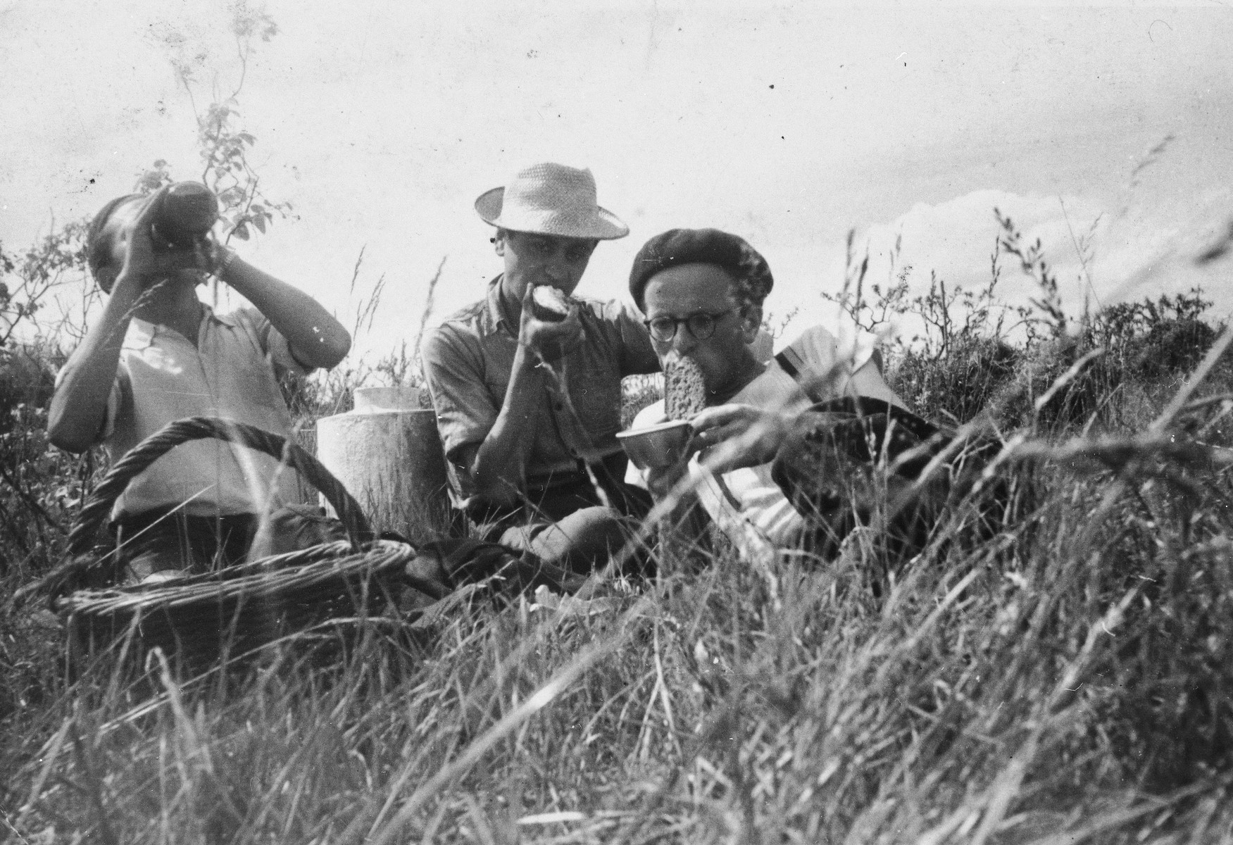 Three Jewish youths, who are living in hiding on a farm in Taluyers, eat a meal while sitting in a field.
