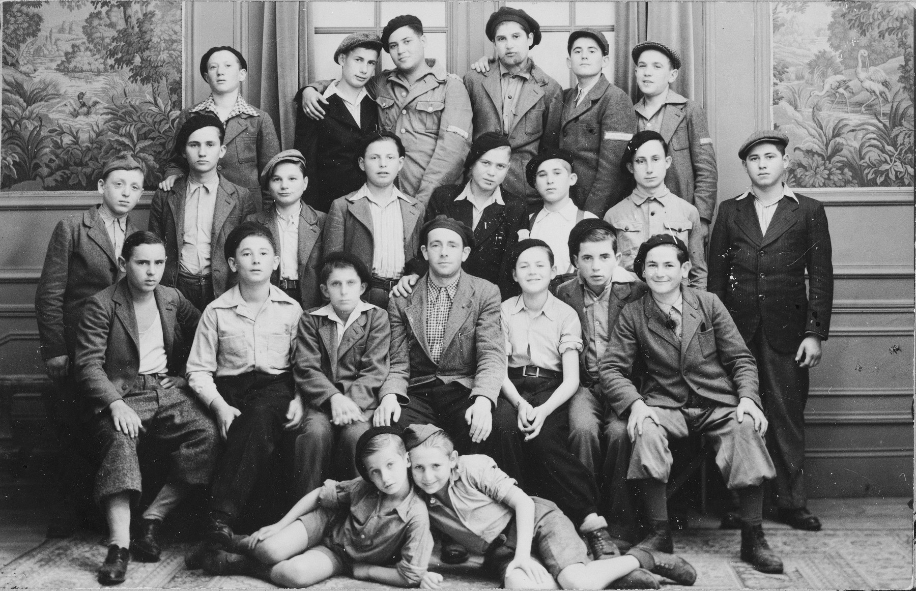 Group portrait of Jewish DP youth who numbered among the Buchenwald children, at an OSE (Oeuvre de Secours aux Enfants) children's home in France [either in Ambloy or Taverny].  The man in the middle is Leo Margolis, a German Jew who was in Buchenwald for approximately six years and helped care for the children.  To his left is Natan Swarc from Piotrkow and on the far right of that row is Josef Szwarcberg.  Lying in front are Izio Rosenman and Jacques (Jakob) Finkelsztajn.