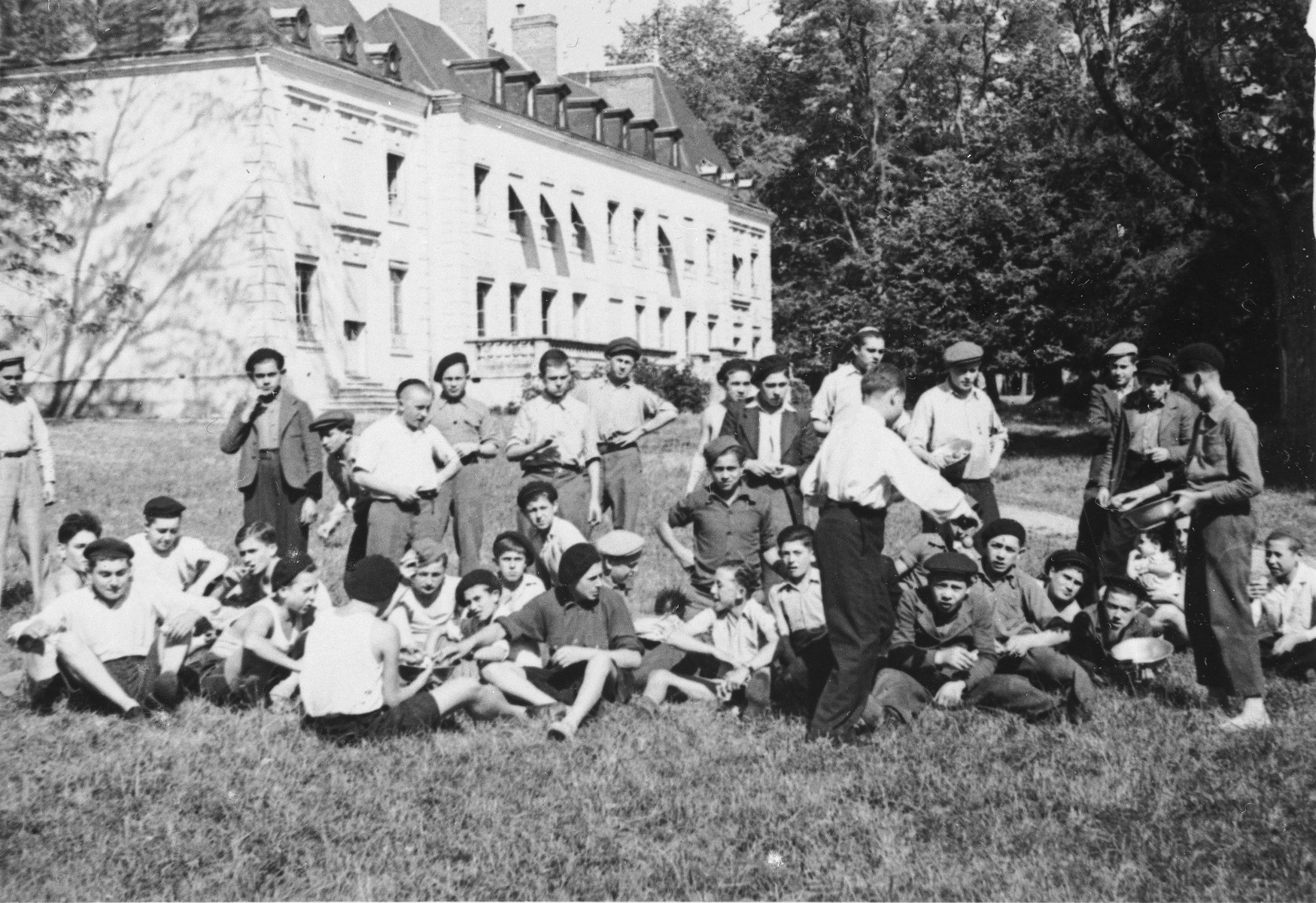 Jewish DP youth who numbered among the Buchenwald children, listen to a boy play the violin while sitting on the lawn at the Chateau d'Ambloy children's home in France, operated by the OSE (Oeuvre de Secours aux Enfants).