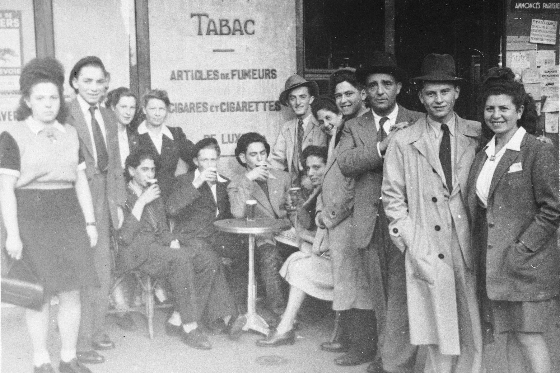 Jewish DP youth who numbered among the Buchenwald children, pose outside a tobacco shop near an OSE (Oeuvre de Secours aux Enfants) children's home in France [either in Ambloy or Taverny].