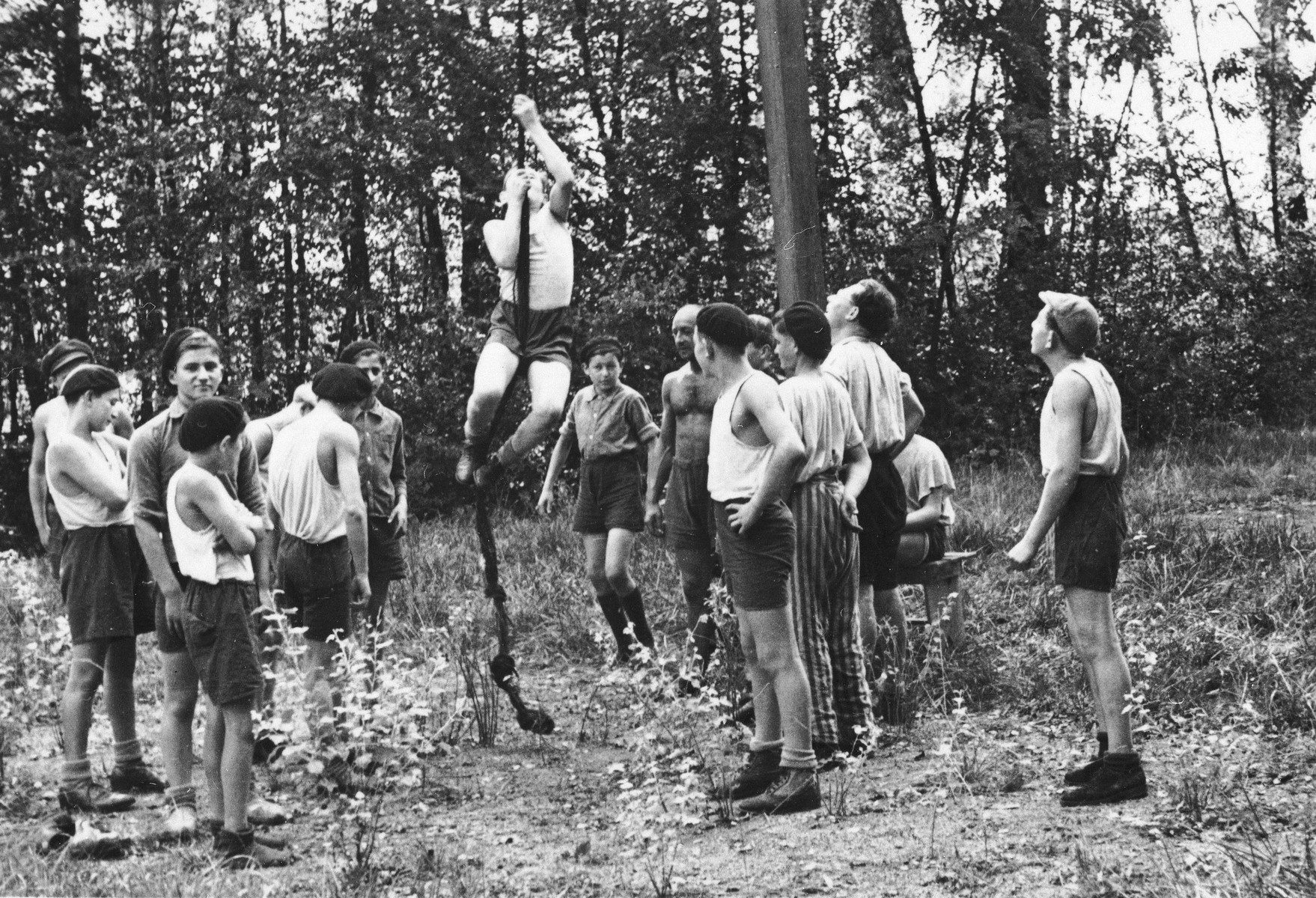 Jewish DP youth who numbered among the Buchenwald children, practice climbing a rope at an OSE (Oeuvre de Secours aux Enfants) children's home in France [either in Ambloy or Taverny].   One of the boys is still wearing the trousers from his concentration camp uniform.