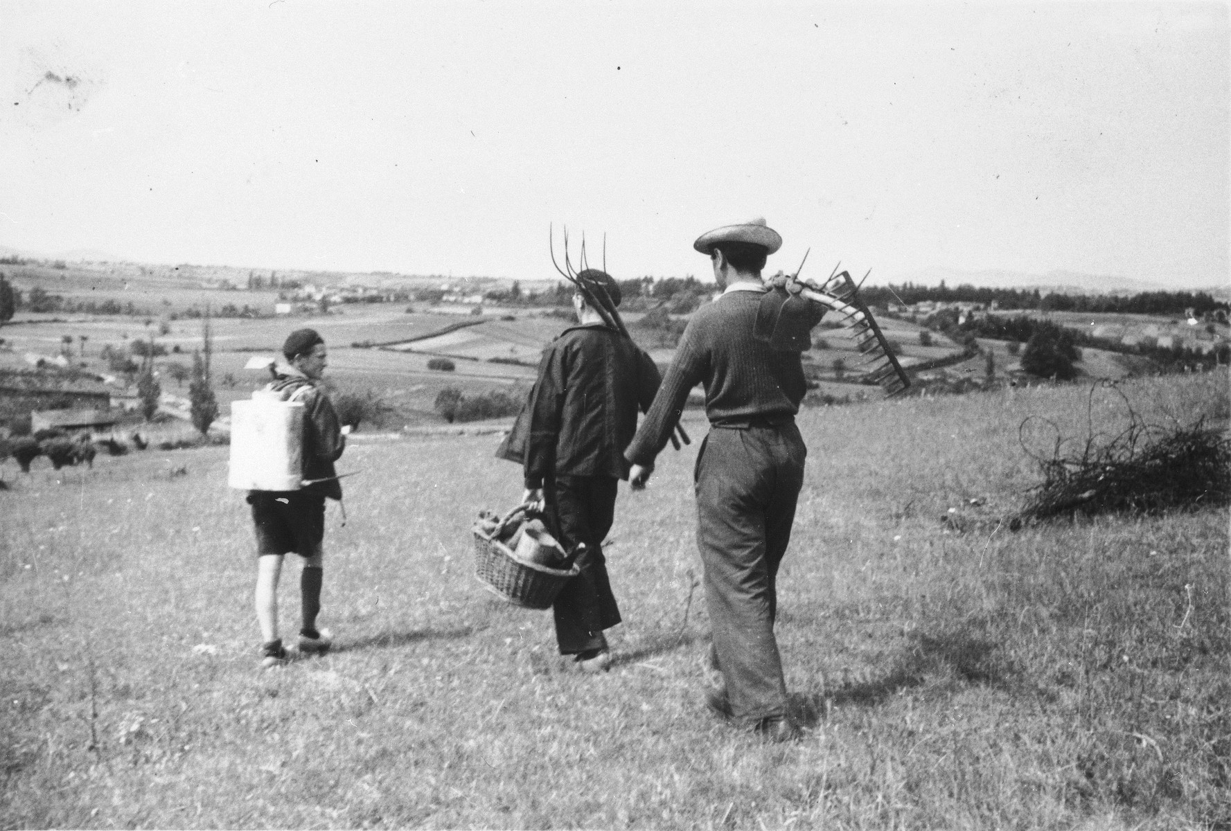 A youth who is living in hiding on a farm in Taluyers, walks through a field with two young men carrying pitchforks.  On the left is Felix Stall who was wounded passing over the Pyrenees but survived the war.